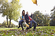 Germany, Cologne, Couple playing in park, smiling, portrait - RHF000045