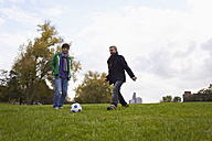 Germany, Cologne, Man playing soccer in park, smiling - RHF000051