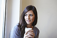 Germany, Cologne, Mid adult woman at window with coffee, smiling - RHF000057