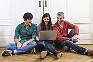 Germany, Cologne, Man and woman using laptop, smiling - RHF000087
