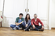 Germany, Cologne, Man and woman sitting near door, smiling, portrait - RHF000090