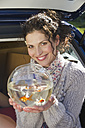 Germany, Bavaria, Grobenzell, Mid adult woman holding goldfish bowl, smiling, portrait - WESTF018112