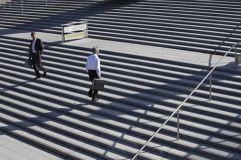 Germany, Bavaria, Munich, Engineers walking on stairs with briefcase - SKF000749