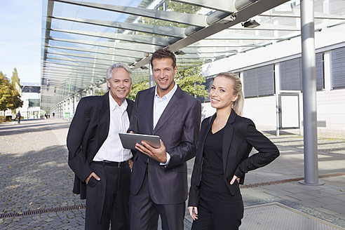 Germany, Bavaria, Munich, Business people using digital tablet, smiling, portrait - SKF000761