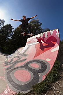 Germany, North Rhine-Westphalia, Ratingen, Skateboarder performing trick on ramp at skateboard park - KJF000155