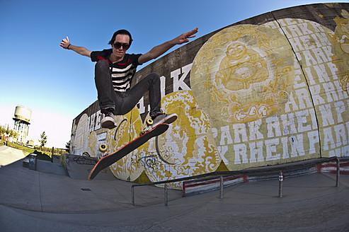Germany, North Rhine-Westphalia, Duisburg, Skateboarder performing trick on ramp at skateboard park - KJF000158