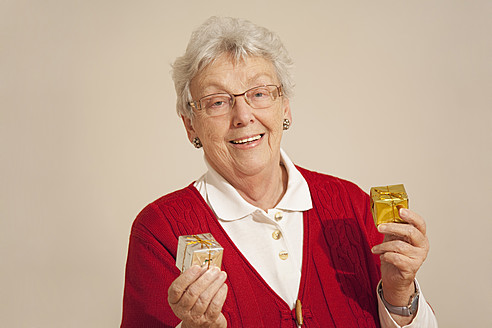Senior woman with gift box during christmas, smiling, portrait - RIMF000097
