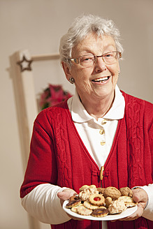 Senior woman with christmas cookies, smiling, portrait - RIMF000099