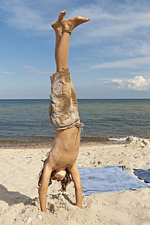 Sweden, Girl performing handstand at beach - SHF000558