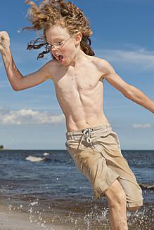 Sweden, Boy running on beach near Borrby - SHF000568
