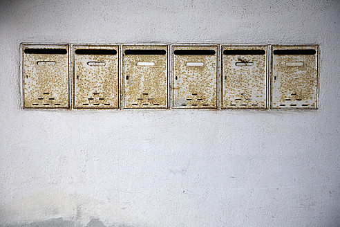 Germany, Bavaria, Wuerzburg, Row of old rusty mailboxes - NDF000243