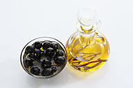 Black olives in glass bowl and bottle of olive oil on white background - CSF015627