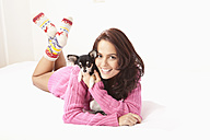 Young woman with chihuahua on bed, smiling, portrait - MAEF004069