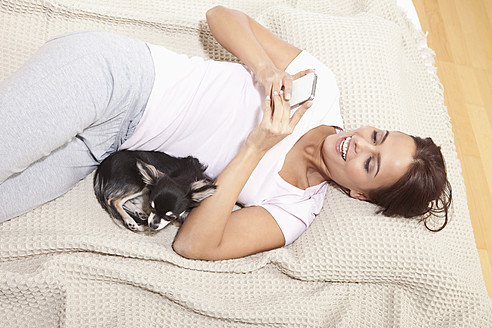 Young woman using phone with chihuahua, smiling - MAEF004082