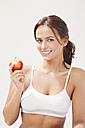 Young woman with apple, smiling, portrait - MAEF004105