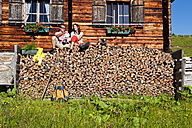 Austria, Salzburg, Couple sitting on logs by hut - HHF003798