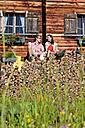 Austria, Salzburg, Couple sitting on logs by hut - HHF003800
