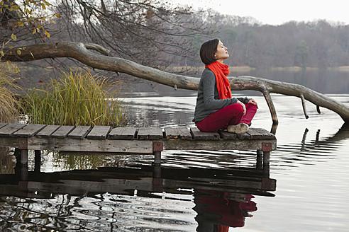 Germany, Berlin, Wandlitz, Mid adult woman sitting on pier - WESTF018287