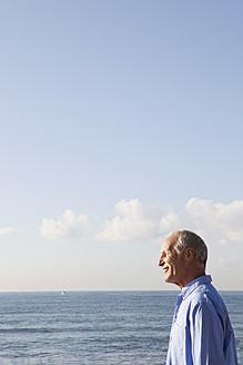 Spain, Mallorca, Senior man standing at sea shore - SKF000788