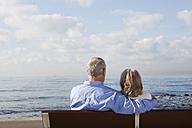Spain, Mallorca, Senior couple sitting on bench at sea shore - SKF000806