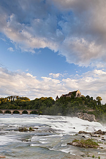 Switzerland, Schaffhausen, View of waterfall and castle at dusk - SH000625