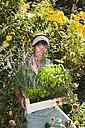 Austria, Salzburg, Flachau, Young woman in garden, smiling, portrait - HHF003863