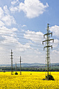 Germany, Bavaria, View of electricity pylon in rapeseed field - FOF003861