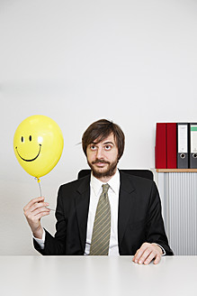 Germany, Businessman holding smiley face balloon - ANBF000071