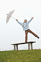 Germany, Bavaria, Girl standing on bench and holding umbrella, smiling - RUEF000835