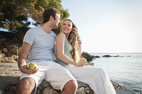 Spain, Mallorca, Couple sitting on beach, smiling - MFPF000006
