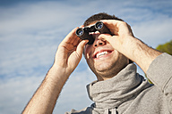 Spain, Mallorca, Young man looking through binocular, smiling - MFPF000018