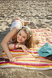 Spain, Mallorca, Teenage girl lying on beach, smiling - MFPF000021