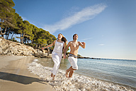 Spain, Mallorca, Couple running along beach - MFPF000024
