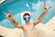 Spain, Mallorca, Young man with funny glasses on diving board, smiling - MFPF000036