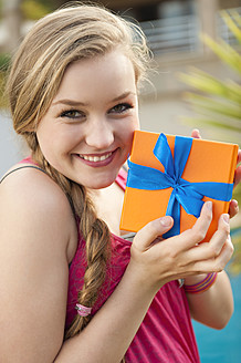 Spain, Mallorca, Teenage girl holding gift box, smiling, portrait - MFPF000042