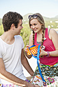 Spain, Mallorca, Young man giving present to teenage girl, smiling - MFPF000051