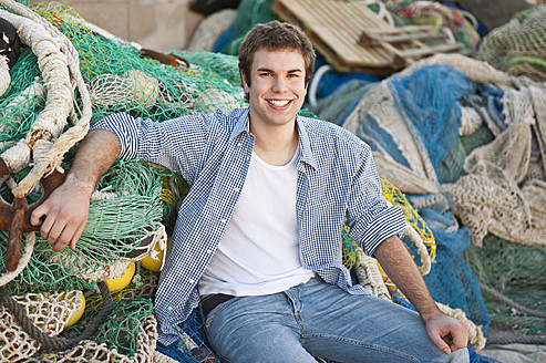 Spain, Mallorca, Young man at harbour with fishing nets, smiling, portrait - MFPF000063