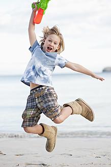 Spain, Mallorca, Boy with water gun on beach, portrait - MFPF000087