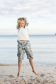 Spain, Mallorca, Boy with water gun on beach, portrait - MFPF000090
