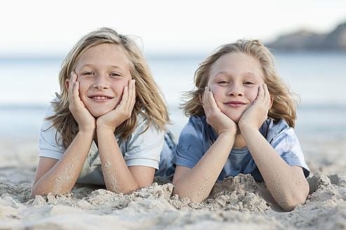 Spain, Mallorca, Children lying in sand on beach, smiling, portrait - MFPF000096