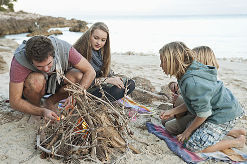 Spain, Mallorca, Friends preparing camp fire on beach - MFPF000105