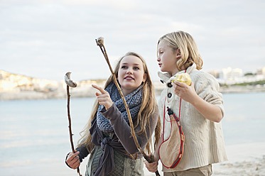 Spain, Mallorca, Friends looking at grilled sausages on beach - MFPF000108