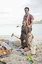 Spain, Mallorca, Friends with sausages at camp fire on beach - MFPF000111