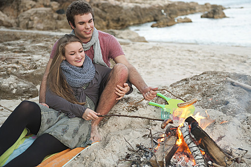 Spain, Mallorca, Couple preparing sausages on beach, smiling - MFPF000114