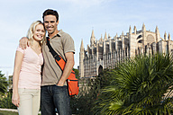 Spain, Mallorca, Palma, Couple standing with St Maria Cathedral in background, smiling, portrait - SKF000875