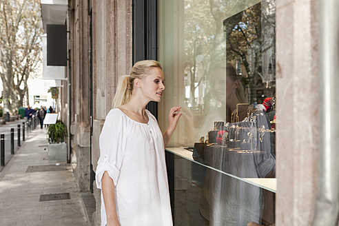 Spain, Mallorca, Palma, Young woman looking in shop window - SKF000914