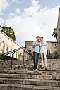 Spain, Mallorca, Palma, Couple with guidebook, smiling - SKF000917