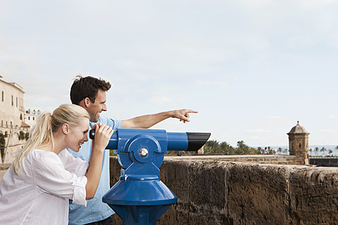 Spain, Mallorca, Palma, Couple looking through telescope - SKF000926