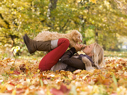 Austria, Young woman playing dog on autumn leaf - WWF002155