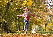 Austria, Teenage girl running with dog on autumn leaf - WWF002160